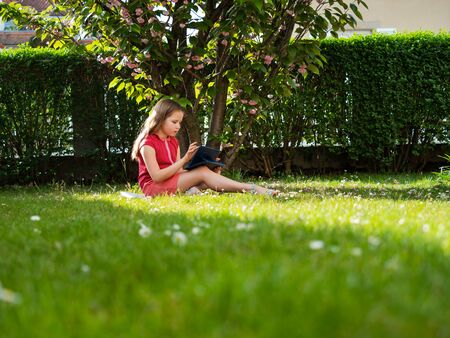 Distance learning during the quarantine period for the virus Covid-19. Cute little schoolgirl with long hair is studying from home, sitting in the garden on the grass. Uses a tablet and remote work via the Internet. Foto de archivo