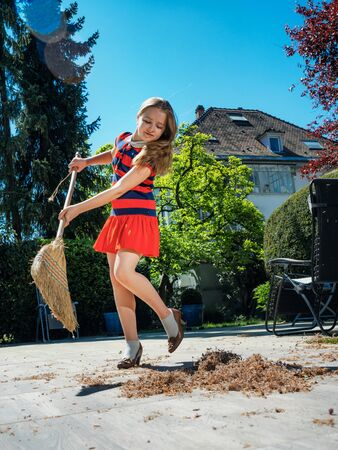 A schoolgirl poses with a broom and in her mother's shoes in the yard. Housekeeper. Sweeping in the garden. Sunny weather. Joyful childhood. Standard-Bild