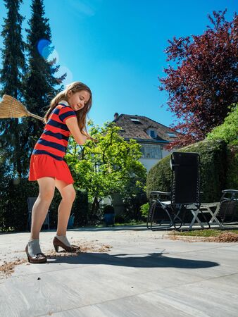 A schoolgirl poses with a broom and in her mother's shoes in the yard. Housekeeper. Sweeping in the garden. Sunny weather. Joyful childhood. Banco de Imagens