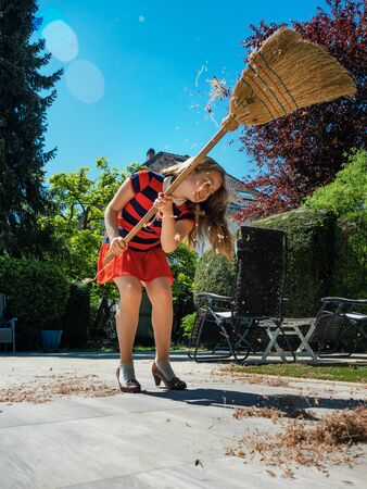 A schoolgirl poses with a broom and in her mother's shoes in the yard. Housekeeper. Sweeping in the garden. Sunny weather. Joyful childhood.