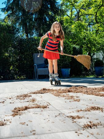 A schoolgirl poses with a broom in the yard, while rollerblading. Housekeeper. Sweeping in the garden. Automation of cleaning and turning it into entertainment. Sunny weather. Joyful childhood.
