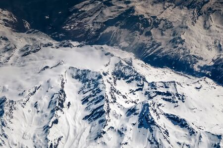 The view from the plane on the snowy tops of the Alpine mountains. France Standard-Bild