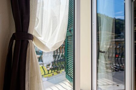 The morning sun breaks through the ajar curtains into the house. Comfort and warmth of the apartment. The bright sun promises a nice warm day.
