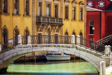 Tourist view of Venice. Channels with reflections. Street lights and colorful houses in the bright sun. Comfort and tranquility. Italy. Standard-Bild