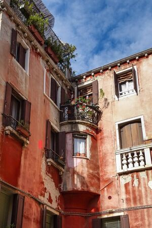 Tourist view of Venice. Channels with reflections. Street lights and colorful houses in the bright sun. Comfort and tranquility. Italy. 免版税图像