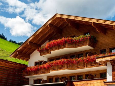 Balconies and terraces decorated with colorful potted flowers in an alpine resort in Austria. Grossarl.