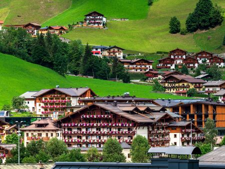 Green hills of an alpine resort in Austria in summer. Small village, hotels and chalets, all in colors. Beautiful terraces and solar panels on the roofs. The proximity of civilization and pure nature. Grossarl.