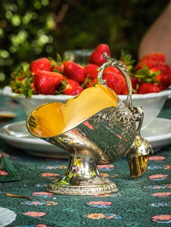 Silver sugar bowl in the shape of a basket for coal. Antique item for the table. Elegant rich dishes for decorating a feast. Strawberries for dessert. France.