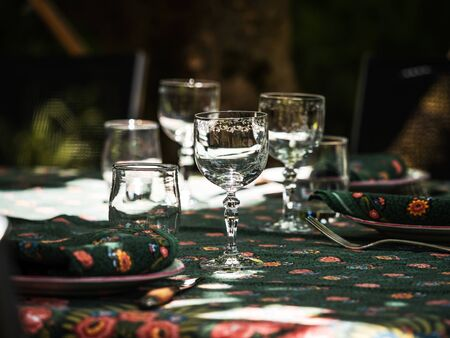 A simple but elegant tablecloth and cutlery laid out on it. Crystal glasses in the sun. Everything is ready for lunch in the garden.France.