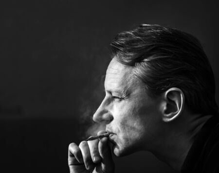 A man with a cigarette. Hard contrast of sunlight. Smoking and health. Black and white.