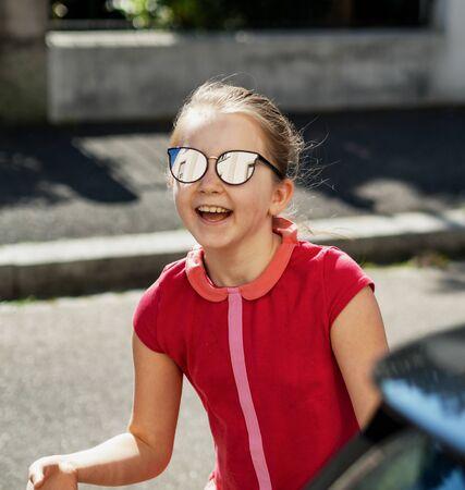 Emotional photos of a schoolgirl girl who runs along the street in the bright sun. France Standard-Bild