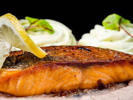 Fried salmon, red fish, with Georgian sauce. Isolated on black background.