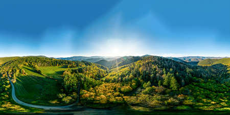 View above a multi-colored valley in the Vosges. Yellow, orange, red tree crowns. Multicolored autumn vineyards. Sunlit hills.