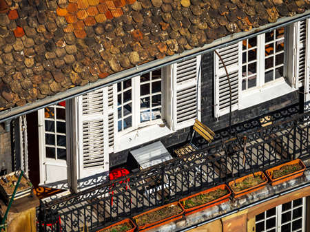 Aerial view of the city of Strasbourg. Sunny day. Red tiled roofs.ÑŽ Houses with a mezzanine. Living quarters under roofs. Small French balconies.