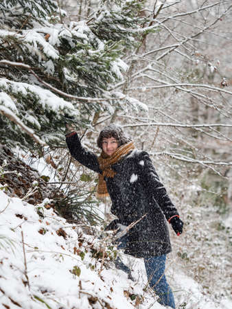 Young girl in a snowy forest. Plays with fresh snow. Snow falls from the trees directly on itself. Winter. Happiness.