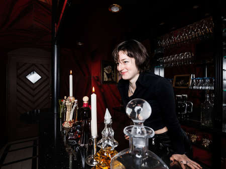A young girl, dressed in a gothic style, poses in a posh alcoholic bar in red and black colors. Contrast. Reklamní fotografie