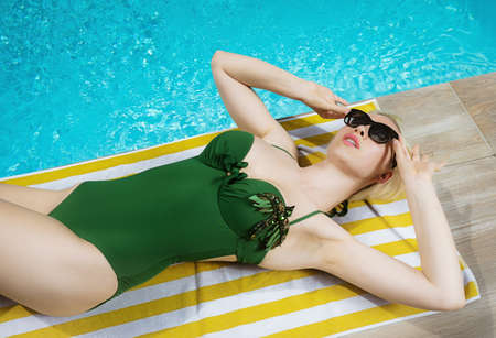 Young beautiful sexy girl enjoying swimming in the private pool and relaxing in the sun. Summertime.
