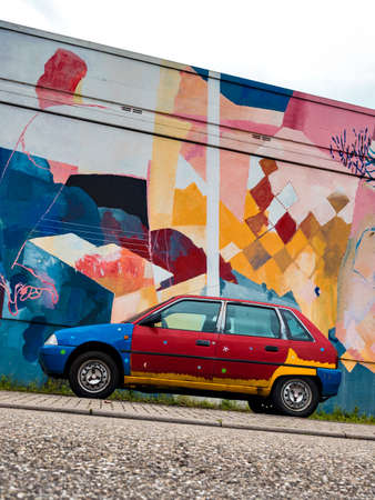 A painted old car against the background of a multi-colored wall. Street art.