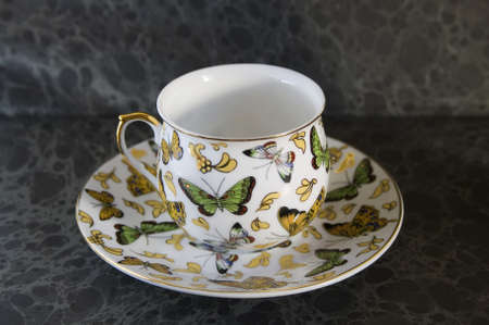 dainty: butterfly on antique teacup on a dark background