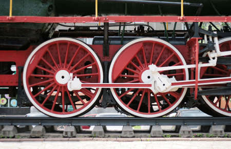 big red locomotive wheels and old rails photo
