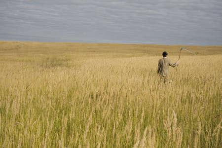 guada�a: hombre de traje y sombrero con guada�a de pie en el campo con c�sped dorado  Foto de archivo