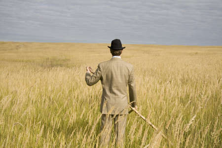 mows: A man mows a grass with a scythe on golden meadow.
