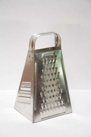 Shiny stainless steel cheese grater on light background photo