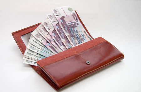 overfilled: orange leather wallet full of one hundred rouble on light background Stock Photo