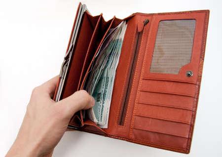 orange wallet full of money and hand photo