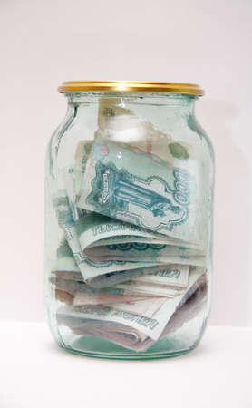reliably: Money in the glass jar on light background Stock Photo