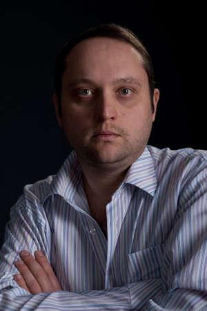 portrait of serious man in white blue shirt studio shot photo