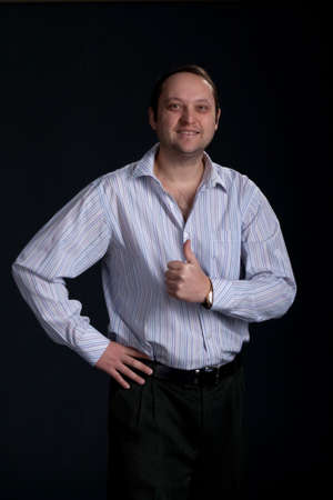A handsome businessman with thumbs up on a dark background photo