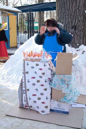 maslenitsa: PENZA, RUSSIA - February 14. Celebration of Shrovetide (Maslenitsa) in russian city woman sell lollipop Editorial