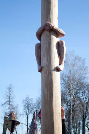 maslenitsa: PENZA, RUSSIA - February 14. Celebration of Shrovetide (Maslenitsa) in russian cityman try to climb up a column (russian entertainment)