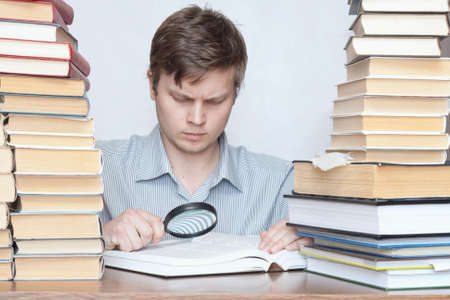 Young surprised student reading book with loupe between books photo