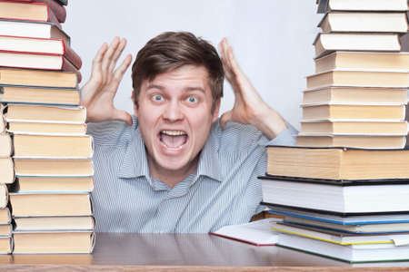 Young crazy student loud shout between books photo