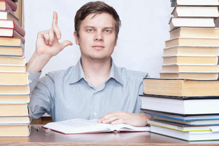 Young serious man show finger to up between books photo