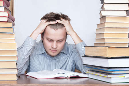Young student sitting between books and reading thinking photo