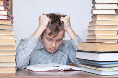 estudiantes medicina: Joven estudiante loco manos m�s cabeza entre libros  Foto de archivo