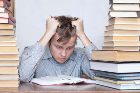 Young crazy student hold hands over head between books