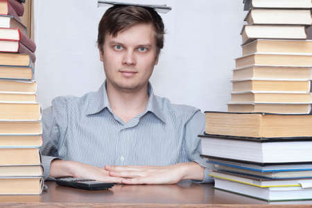 Young student sitting with book on the head between books photo