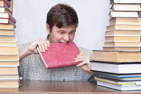 Crazy student gnaws red book between books photo