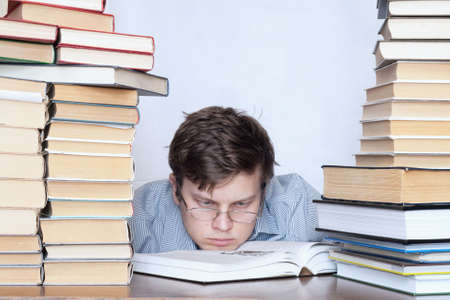medical school: Young tired student with glass sitting between books Stock Photo