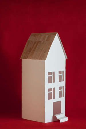 immovable: White paper house with four windows on red background