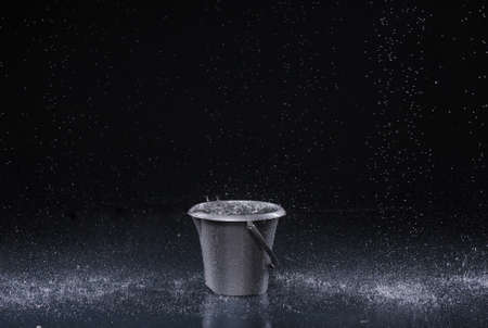seau d eau: Seau avec gouttes d'eau sur fond sombre Banque d'images