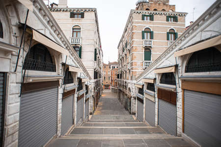 Closed Shops on Rialto Bridge in Venice. Italy. View on Salizzada Pio X Street. Cloudy Sky.