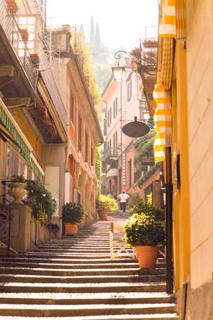 Sunrise on Old Picturesque Street in Bellagio City. Lombardy. Italy. Early Morning without Tourists. Woman Go Up on Staircase.