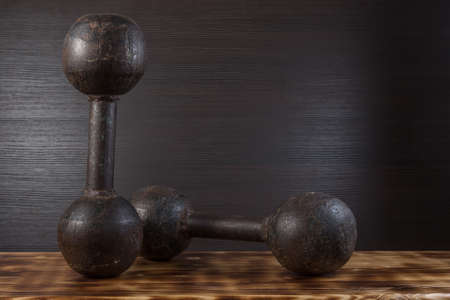 Old dumbbells on wood surface. Dark background.