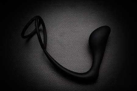 Black silicone prostate massager on black leather. Anal plug. Stock Photo