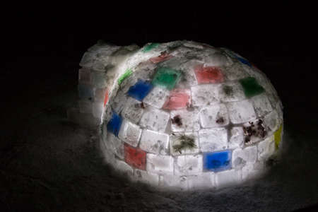 Random color igloo, illuminated from the inside on a dark background.